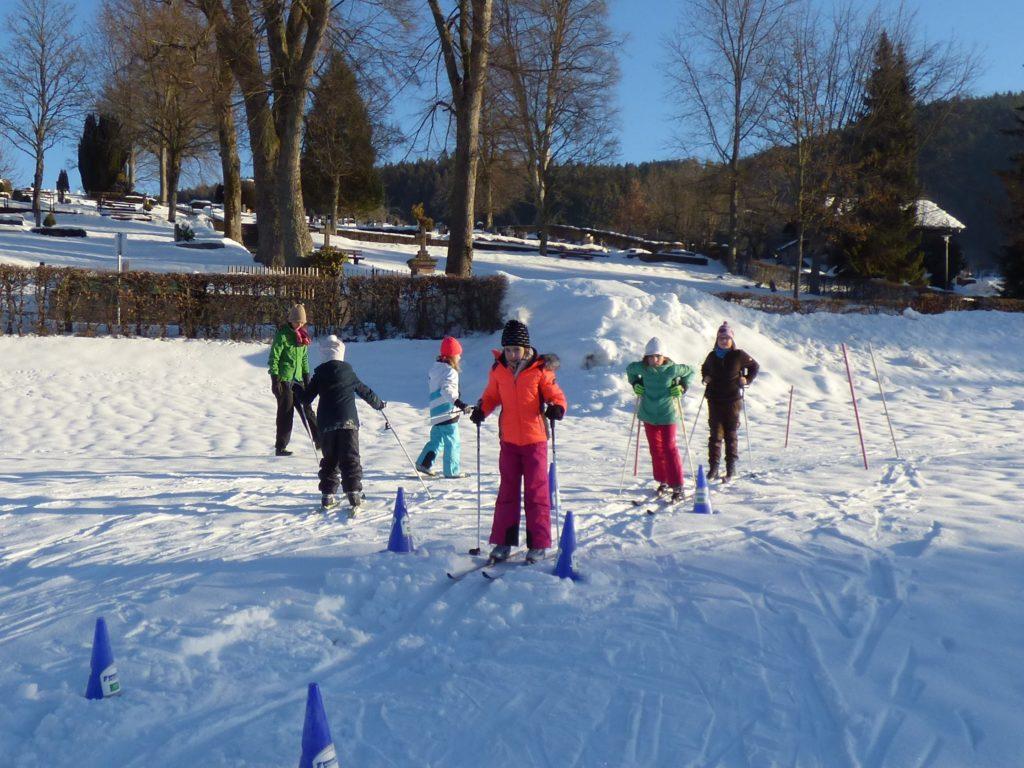Kinder auf schmalen Langlaufskiern fahren auf einer Wellenbahn.